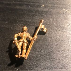 Goldtone knight in armor with sword/flag pin